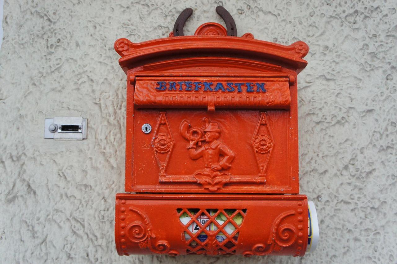 Roter Briefkasten mit Zeitungsrolle